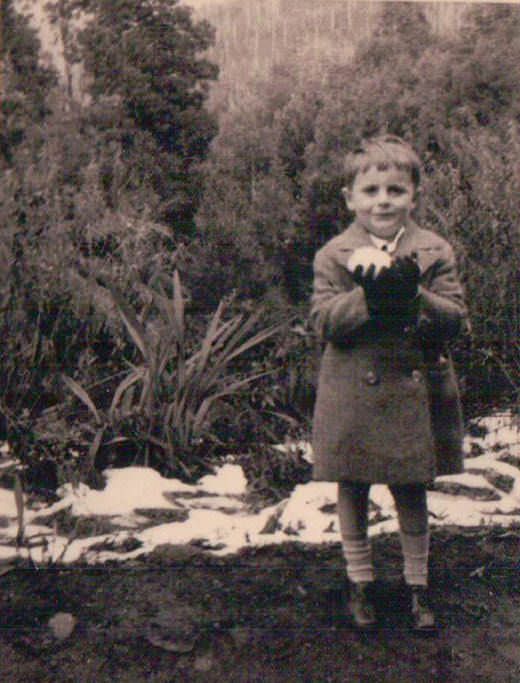 Barry Humphries as a little boy in Australia clutching a rare snowball